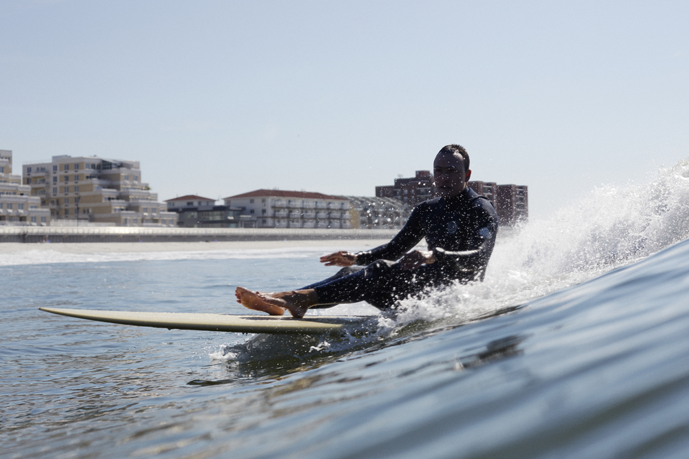 Patience takes many forms. Sometimes it's all about just taking the time to be silly and do things like ride waves on your bum! Here I am riding in to meet a student during a lesson at Long Beach. Photo:  Julien Roubinet