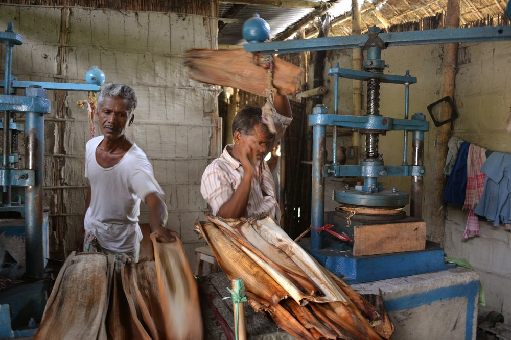 Two men work a pair of presses in a community-run Tamul Plates production unit.