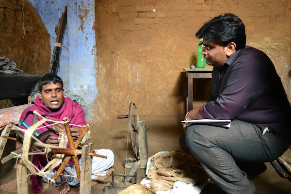 Sanjeev (left) explains the process of spinning bobbins to Upaya's Sriram Gutta. January 2013.