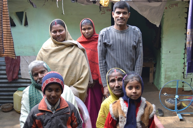 Bindu (seated, bottom left) with his wife, one of his sons, his two daughters-in-law, and his grandchildren pose in front of the family home. January 2013.
