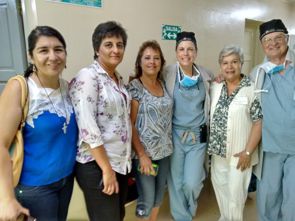 On a March 2016 Gynecologic Mission Trip,  Puente de Solidaridad  staffers (from left) Marcela Canedo and Patricia Vargas and board member Maria Eugenia Rojas (second from right) posed with missioners Dr. Janet Tomezsko and Dr. Ronald Miller. In the center is Genevieve, a patient who told the team about the positive changes in her life thanks to treatment she received in 2014.