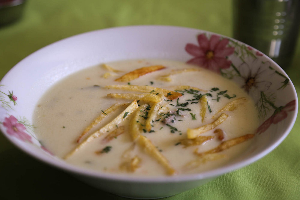 Sopa de maní  (peanut soup), a nourishing broth made from ground peanuts, has a garnish of fried matchstick potatoes.