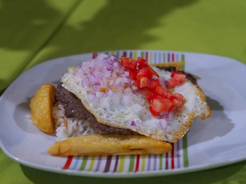 With a name from the Quechua language,  silpancho  is a traditional dish featuring rice, breaded meat, and a fried egg.