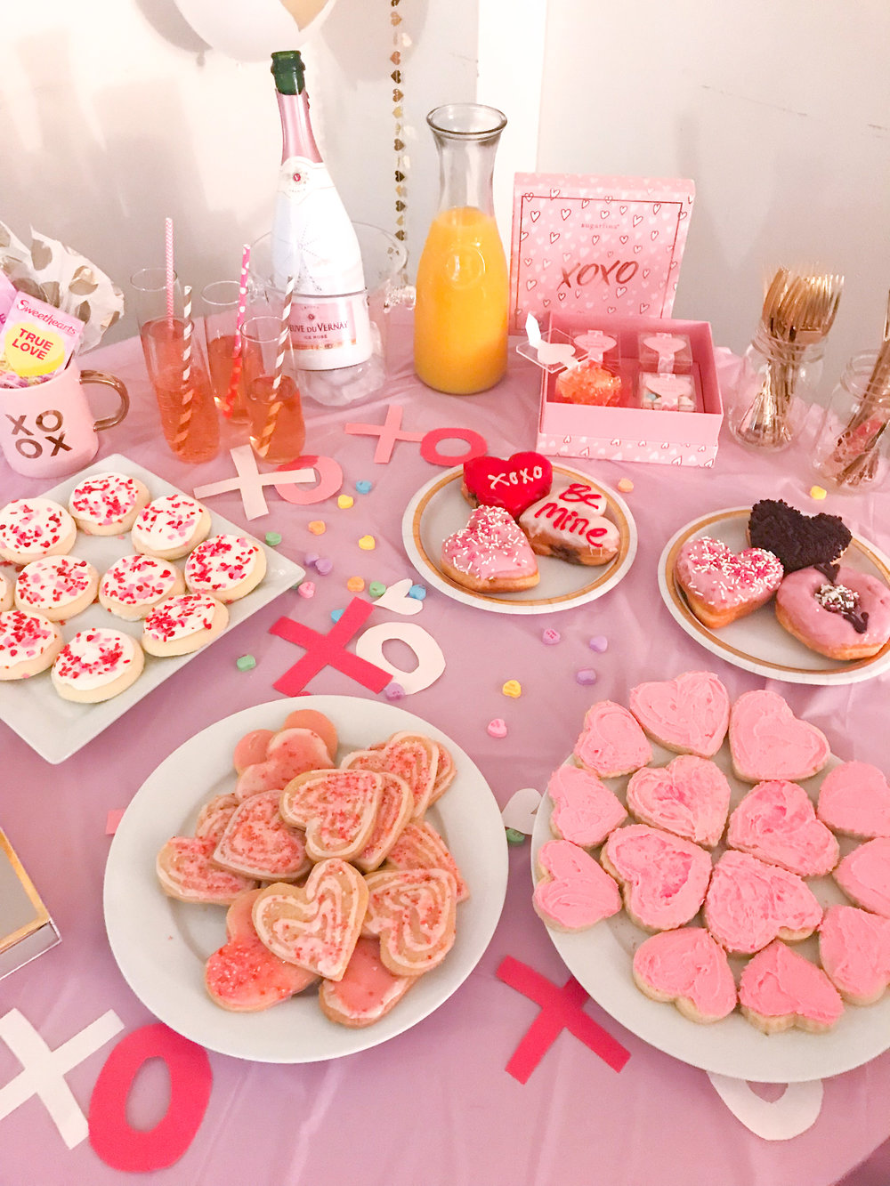 - FoodWe dined on a delish homemade egg bake, quiche, mini bagels and fresh fruit.SweetsWe have some great bakers in our group of friends so many of the cookies were homemade! But we also had some super cute doughnuts from Dunkin and adorable candies from Sugarfina! DrinksTo keep with the pink theme, we drank Veuve du Vernay Icy Rose champagne and had a mimosa bar with classic orange juice and also strawberry, orange and banana (it was the perfect pink color!)GamesWhile sipping and snacking, we spent the day laughing and playing