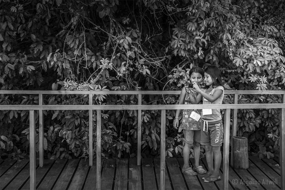 mighty me photographers - Girls in the jungle(Rio Dulce, Guatemala)  11 X 17 PRINT$55  20 X 30 PRINT $105  two girls  REVIEW THEIR PHOTOS on a bridge, nestled in foliage. © Angelina Attwell