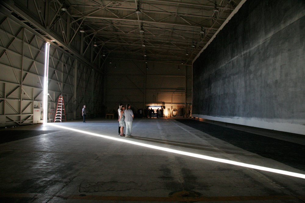 Admiring the Great Picture in the F-18 hanger with a strong beam of natural light framing the viewers.