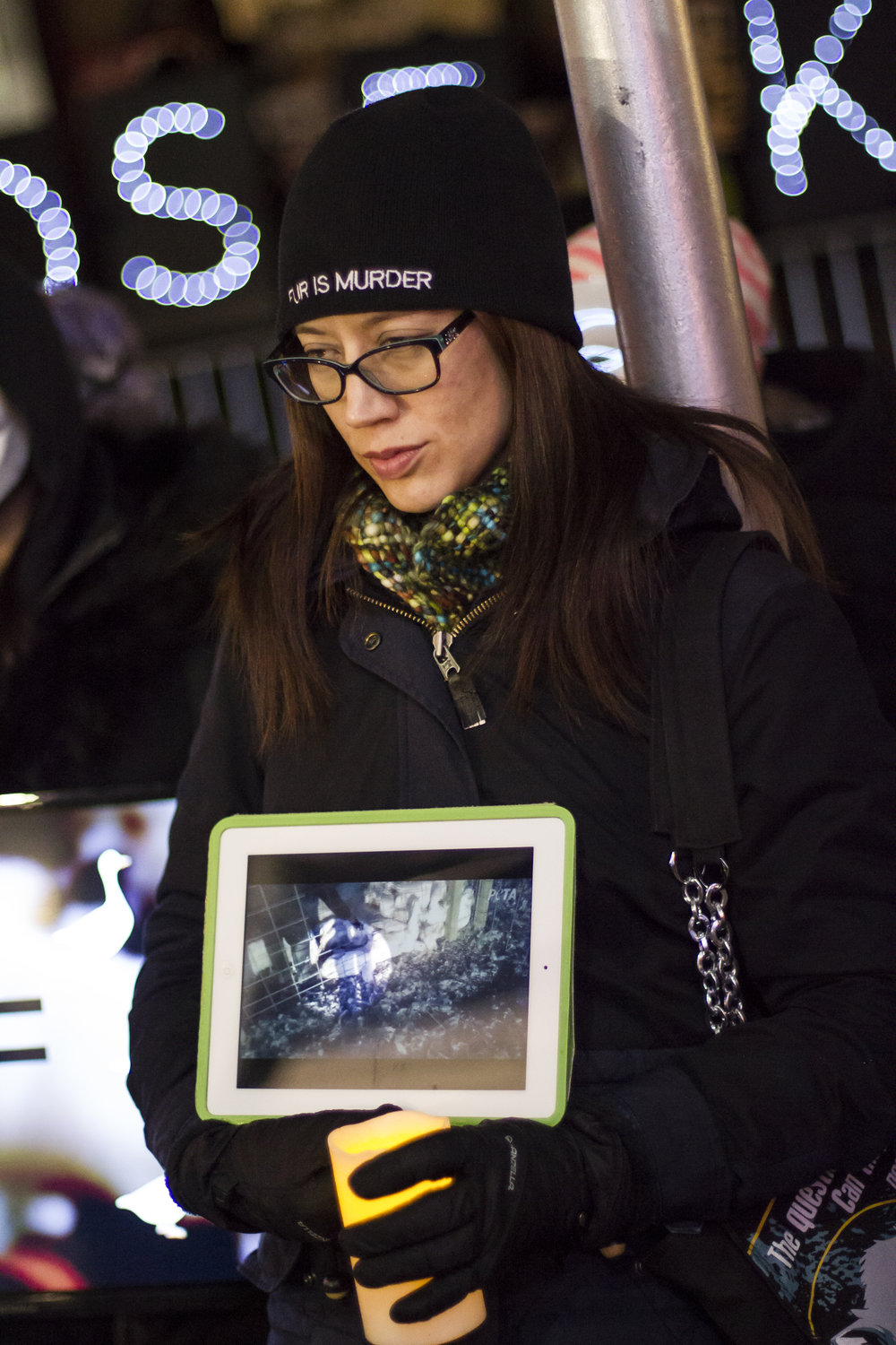 This activist holds an tablet that displays video footage of the barbaric methods used to obtain the body parts used in  Canada Goose  jackets.