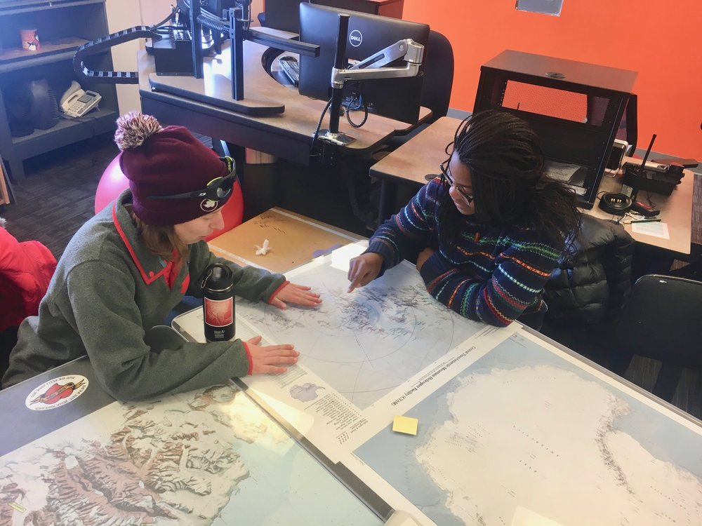 "Anny and Emilie scoping the maps before our meeting with ""MacOps,"" the office in charge of communications with groups out in the field."