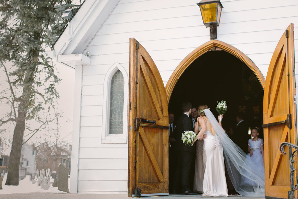 Guests hugging couple at church doorway