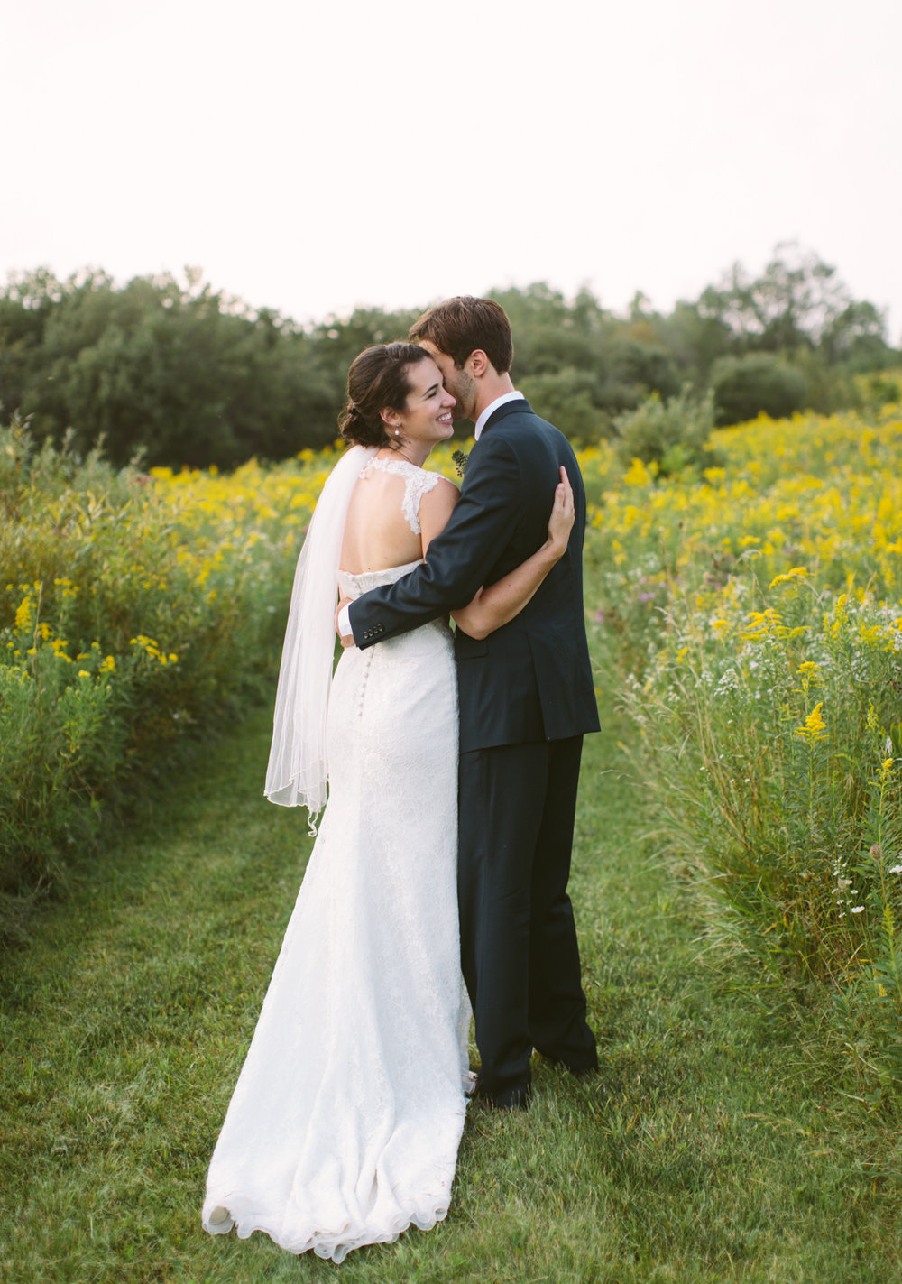 Couple embrace in a field of wild flowers
