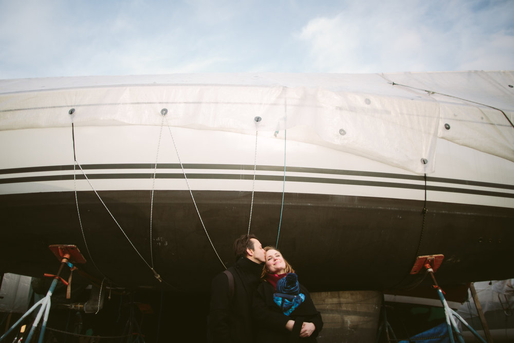 Young couple embracing in front of a boat