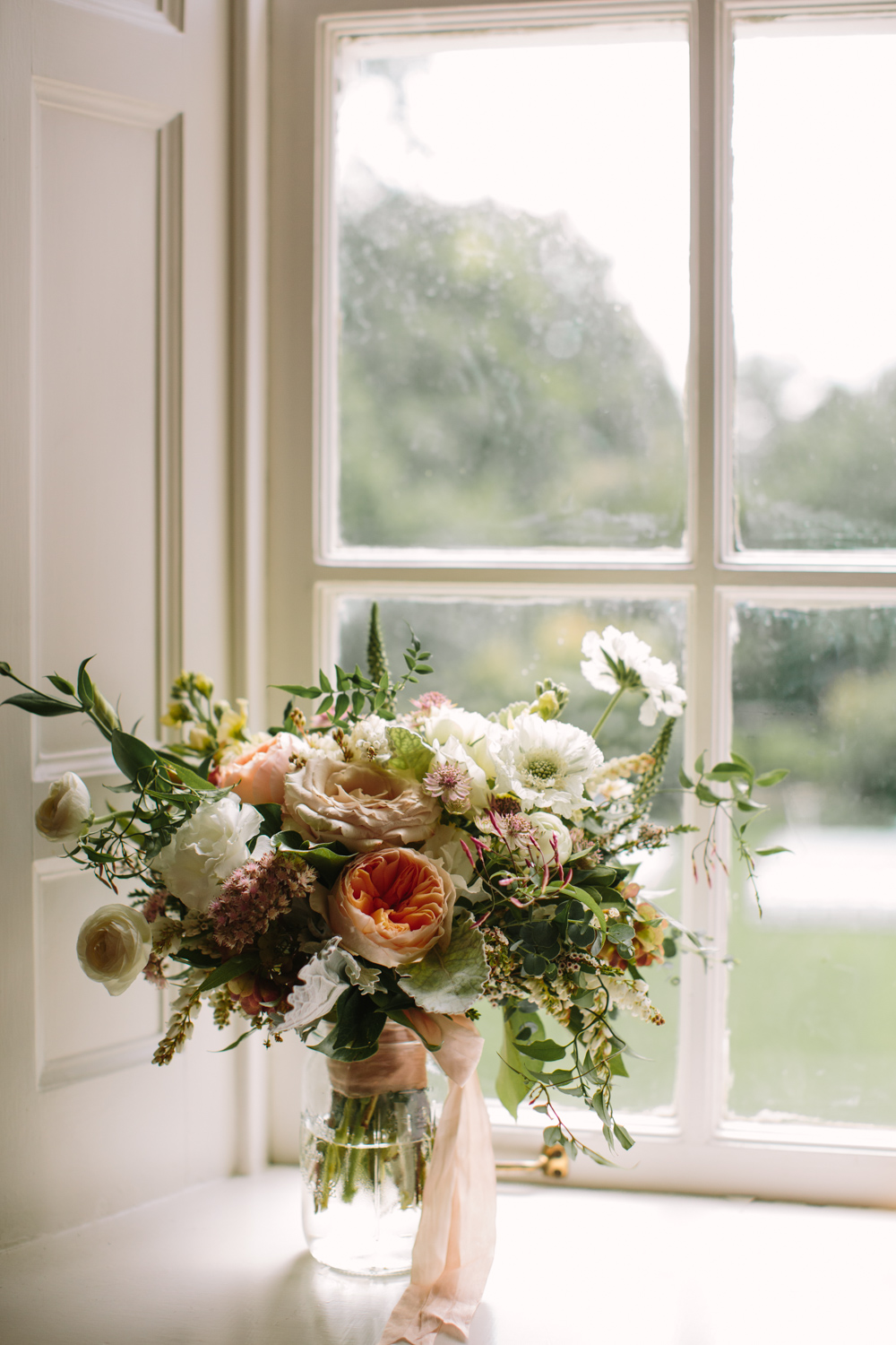Floral bouquet with blush silk ribbons on a windowsill