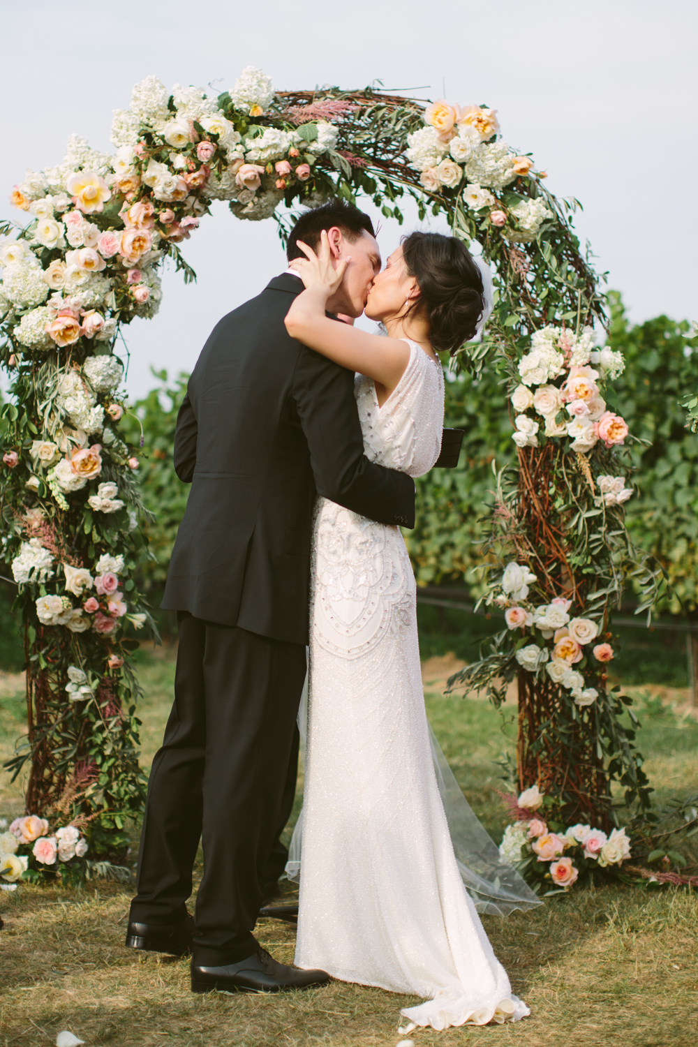 Bride and groom kiss in front of a floral archway