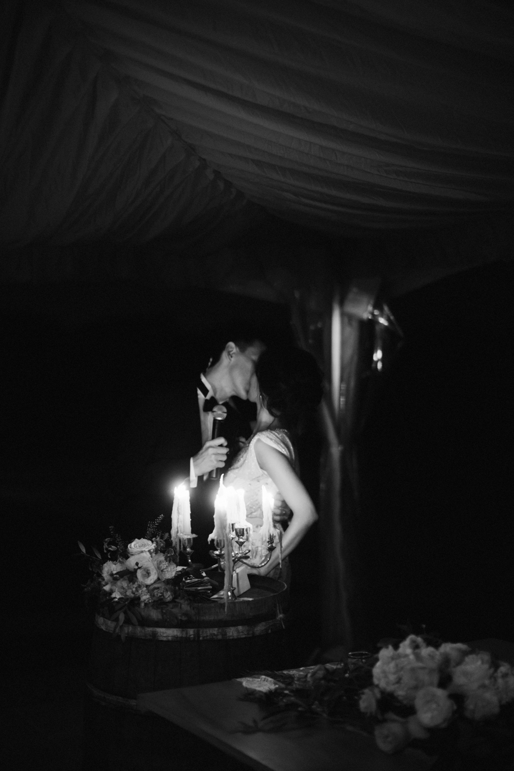 Romantic mid-speech kiss by candlelight