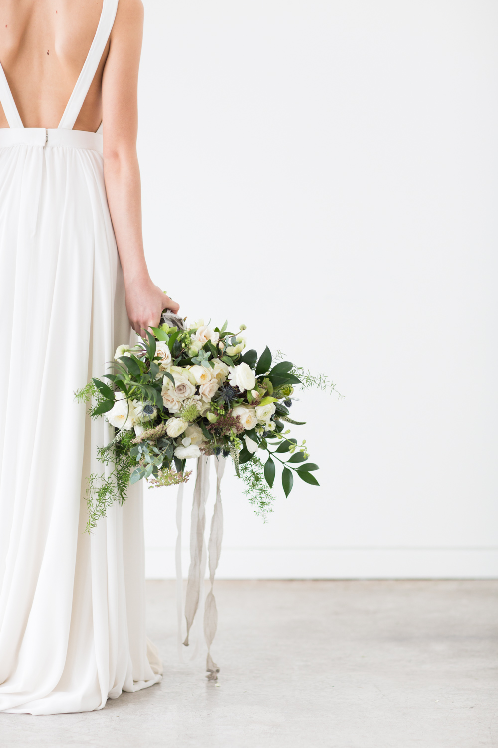 Bride wearing Brianna Truvelle dress holding a green and white minimal bouquet