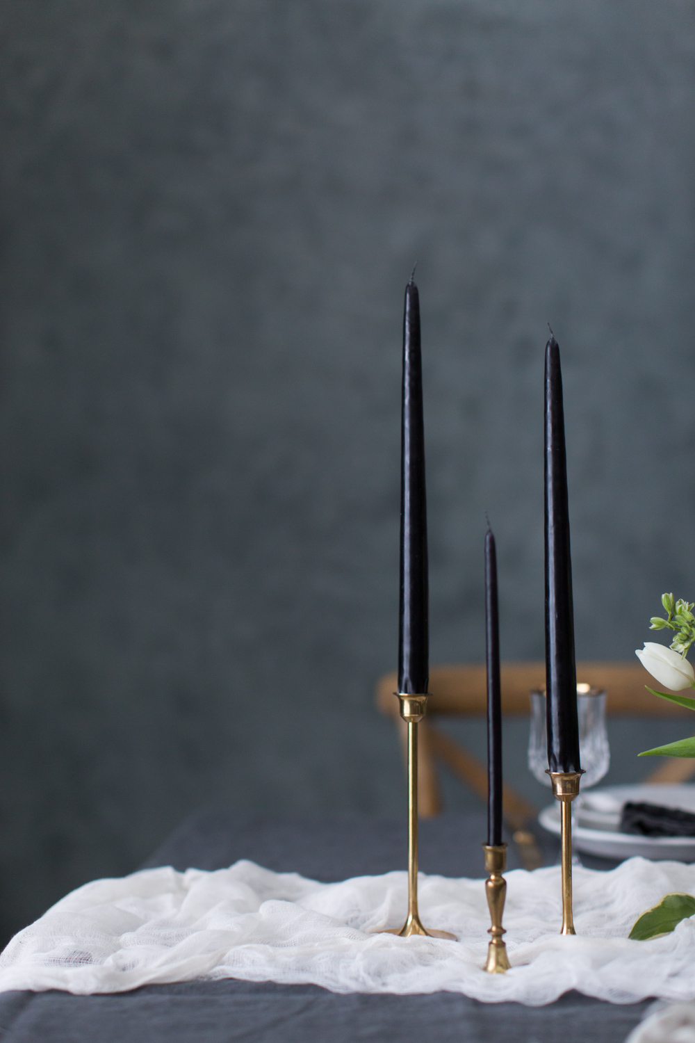 Dark tapered candles on simple brass candlesticks