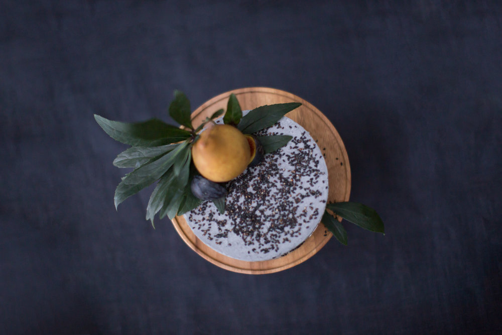 Black sesame cake adorned with pears and figs made by Le Dolci presented on a wooden platter