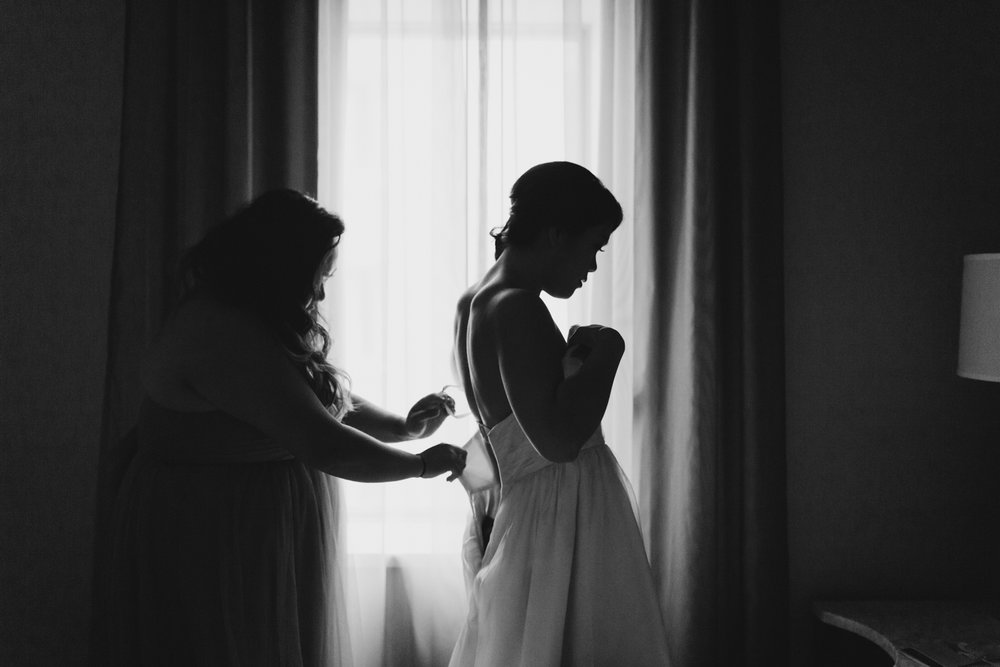Bridesmaid helping bride put on her dress by the window