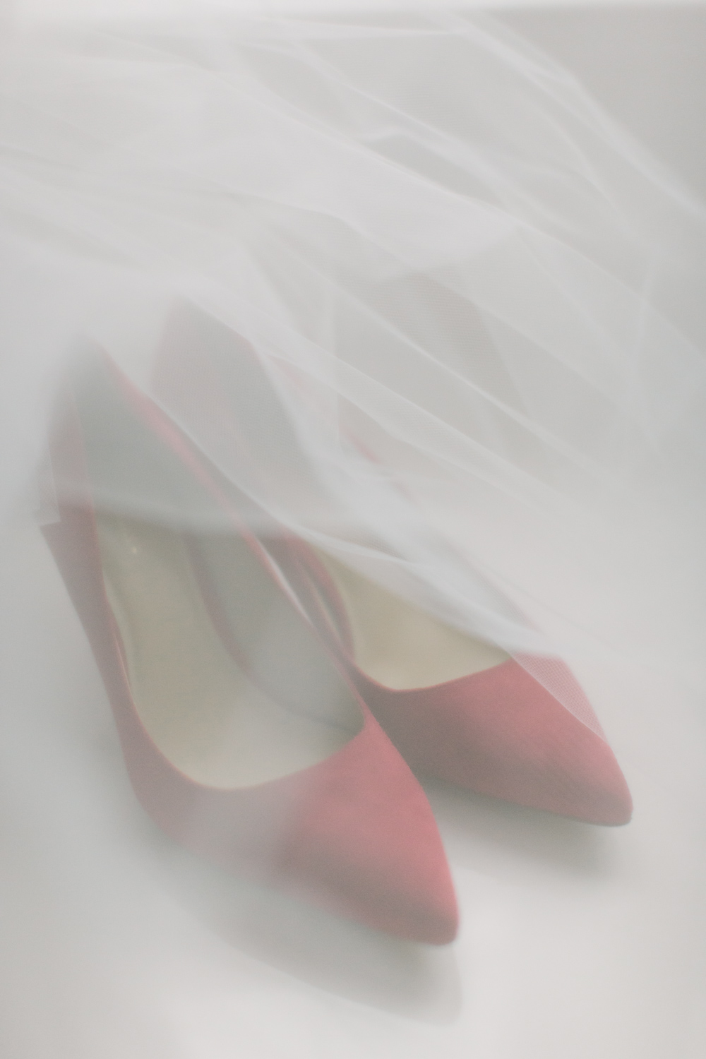 Red wedding shoes under a veil
