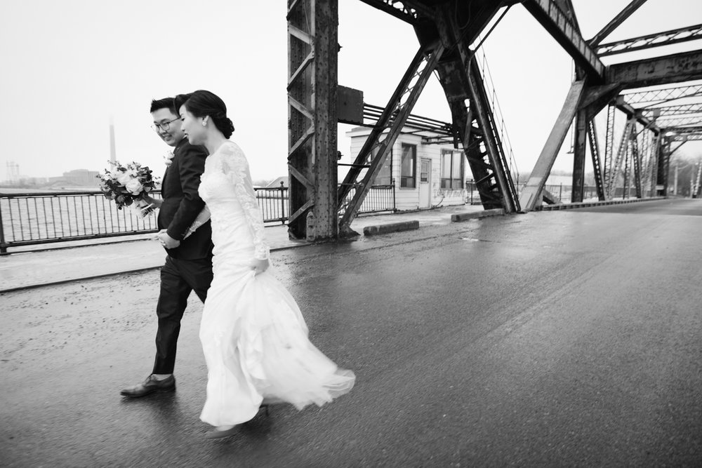 Bride and groom walking on bridge near Cherry Beach in Toronto