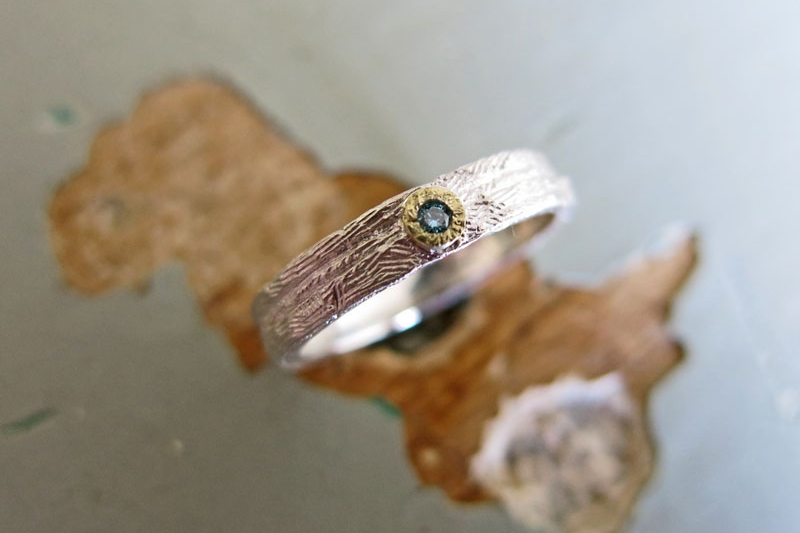 symbiosis wedding ring with blue diamond and sun bezel