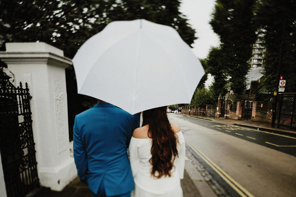059-bride-and-groom-walking-down-the-rain.jpg