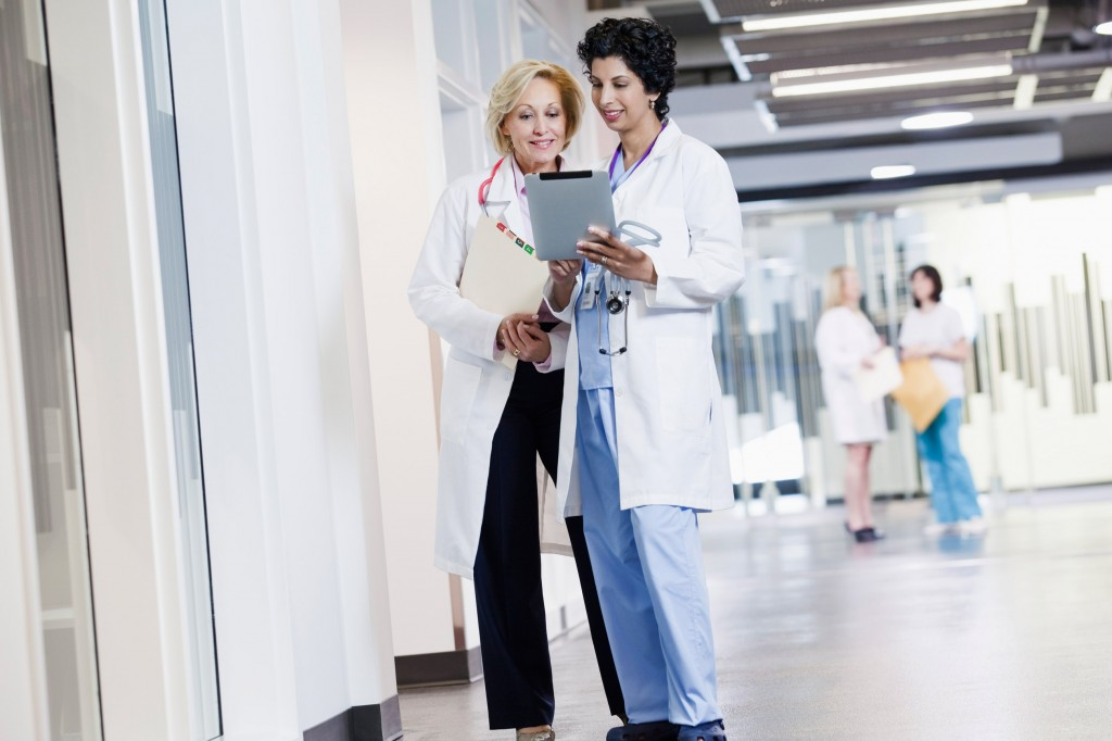 Two female doctors talking in corridor