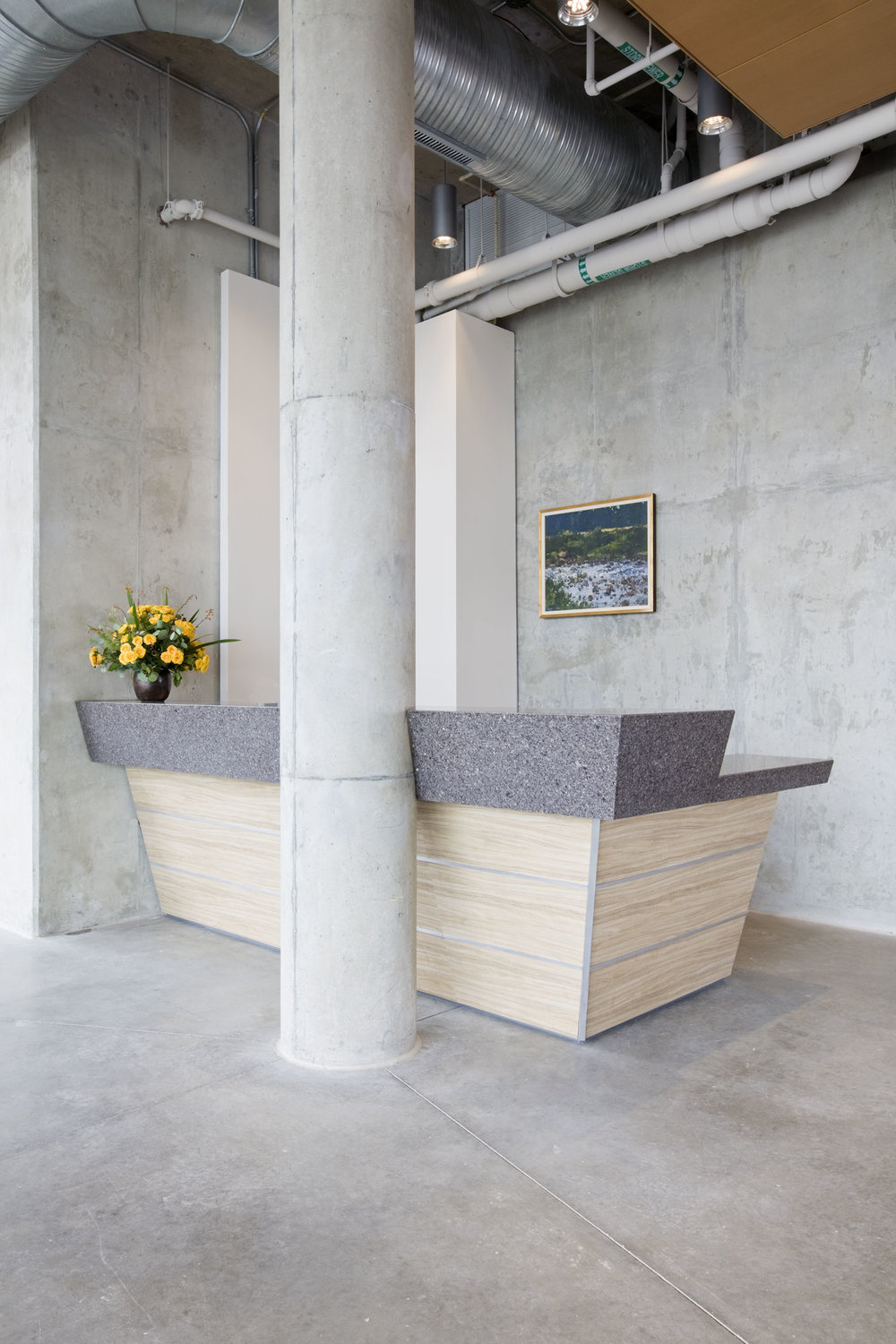 "This beautiful and energetic reception desk is made of concrete and marble and is a masterpiece of complicated lines, angles and cuts. The desk ""explodes"" from its space and nearly bisects the round column. The layers of angles that form the transaction top give way to similar angles in the face portion, now pulling away from the round column."