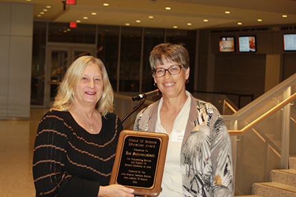 Yvette McCulley (L) accepts the award from Kelen Panec to honor posthumously Joseph Schwanebeck, Director of Education, Science Center of Iowa