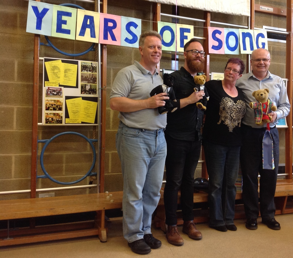 Over the last 21 years Stokes Singers have been led by four Musical Directors, (left to right) Phillip Lawrence, Ben Tansey, Sian Walters and Nick Breeze. At the end of the workshop each was presented with a suitably dressed teddy bear.