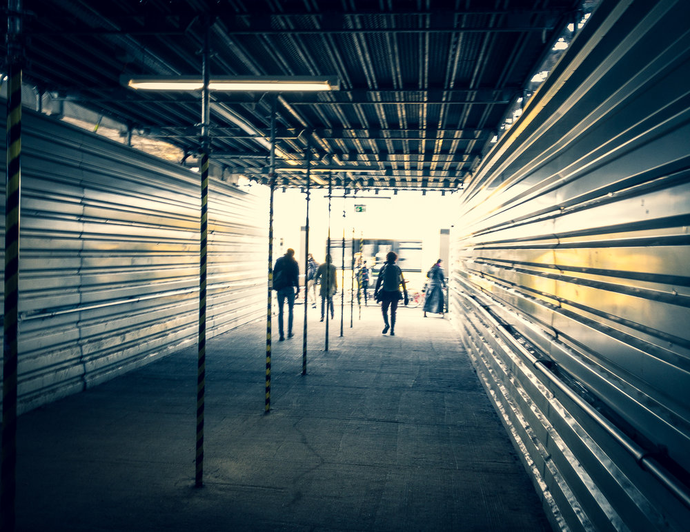 """Into the Light"". Exiting Warshauer Straße S-Bahn station, construction tunnel into the light of the streets."