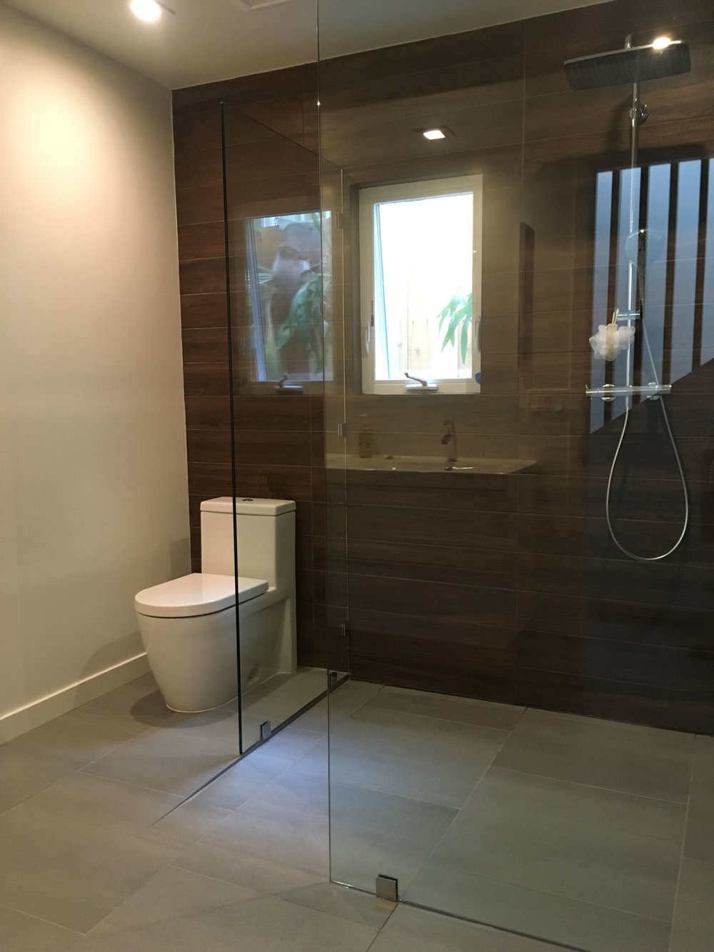 Bath with lateral drain, Duravit toilet, Hansgrohe shower. Ceiling ductwork was rerouted into a soffit above the sink and vanity allowing ceiling height to be raised to 10 ft.