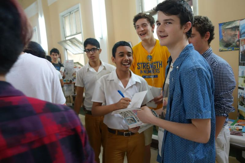 Pierson student Drew Fisher (center right) and isex-Pierson student Jack Muth (right) exchange social media connections with Cuban students at a Havana high school. Peter Solow photo