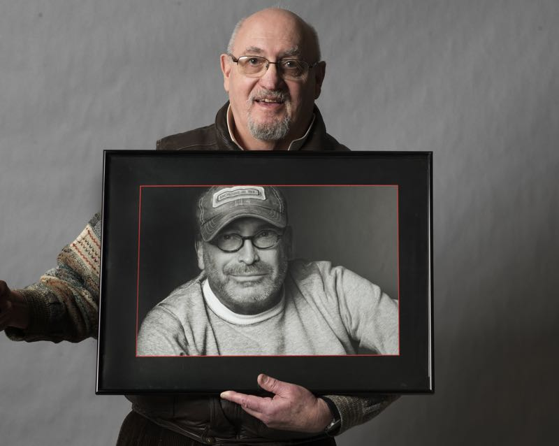 Jonathan Morse holding his portrait of Peter Marcelle.
