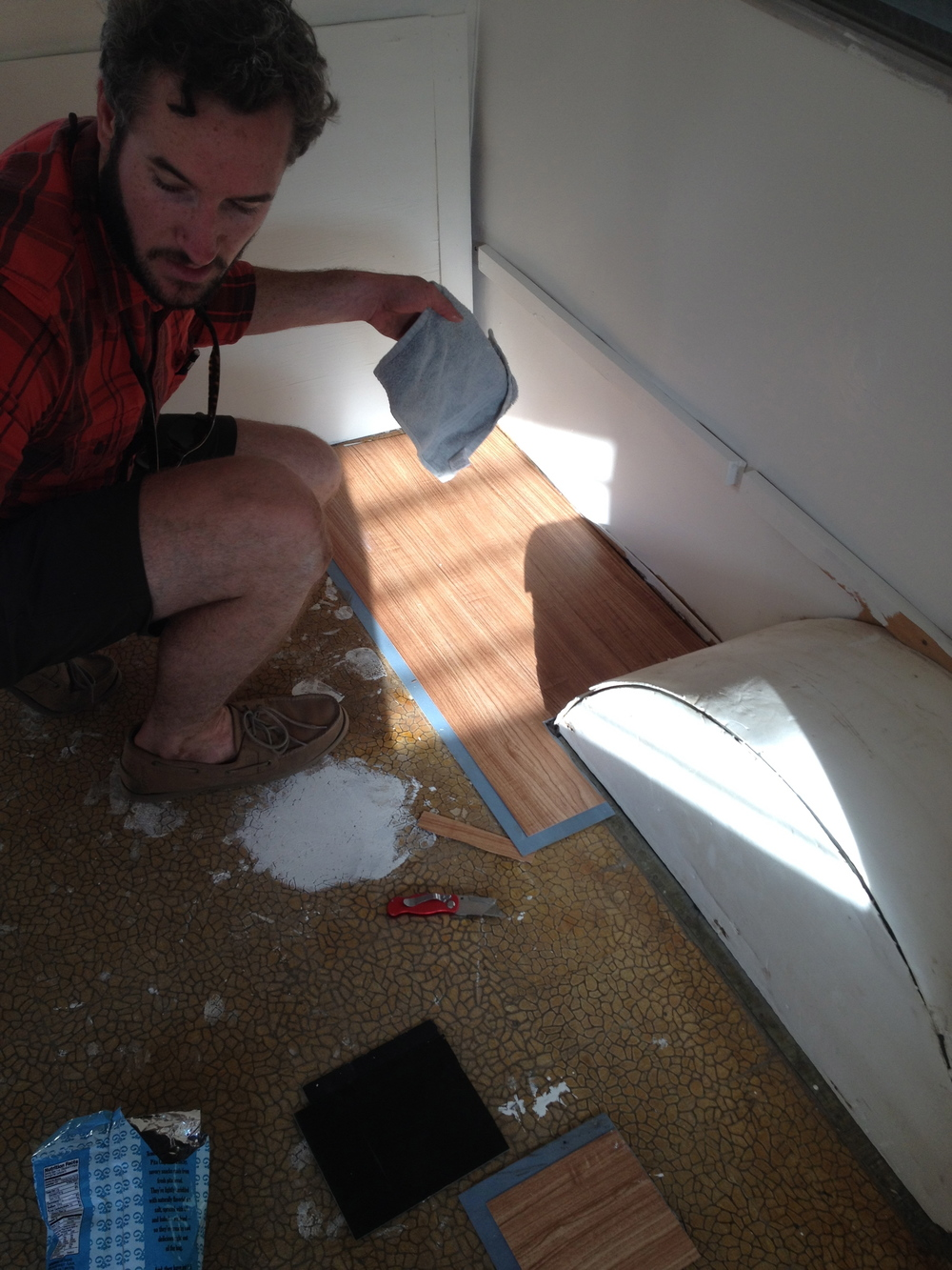 Andrew installs new flooring in the trailer.