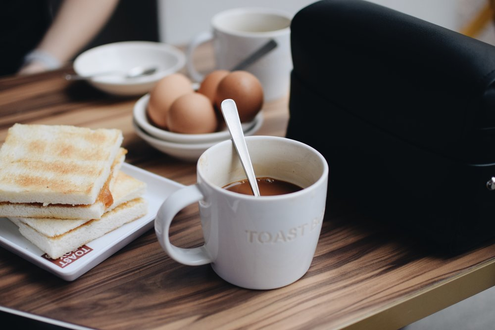 A traditional Singapore breakfast with Toast Box with eggs, kaya toast and a coffee.