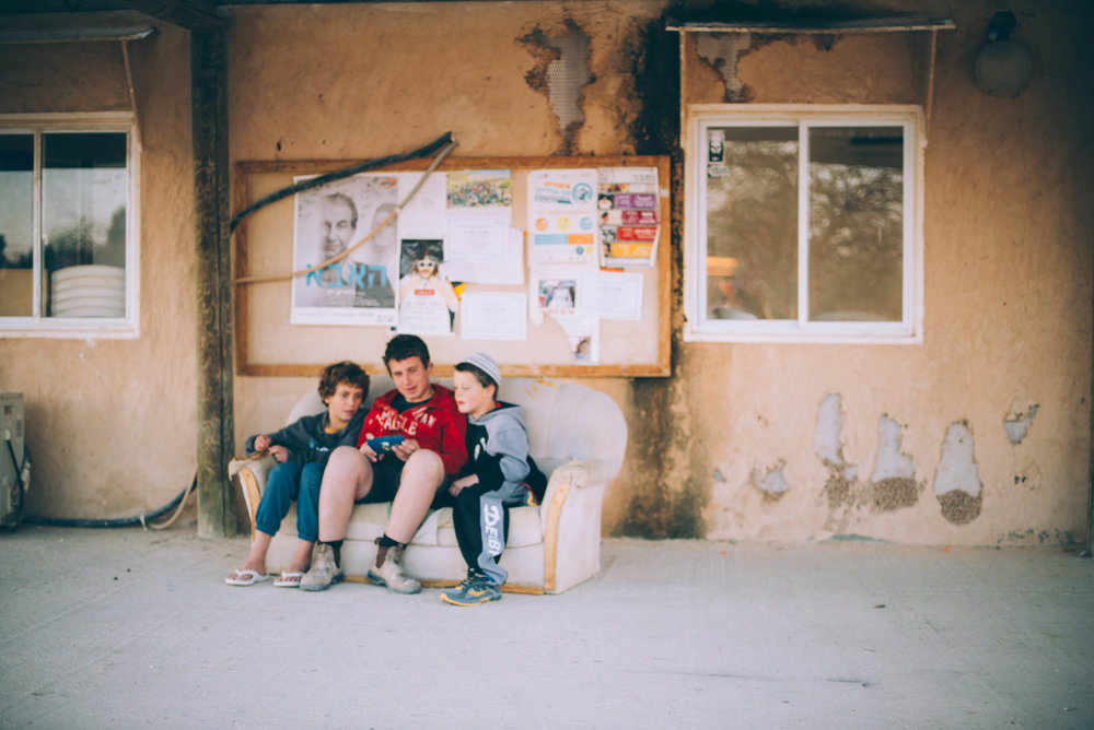 Boys play on their cell phone in Ezuz, Israel.