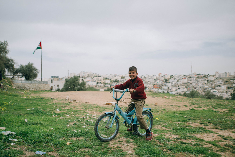 A boy rides his bike in Hebron, Palestine.