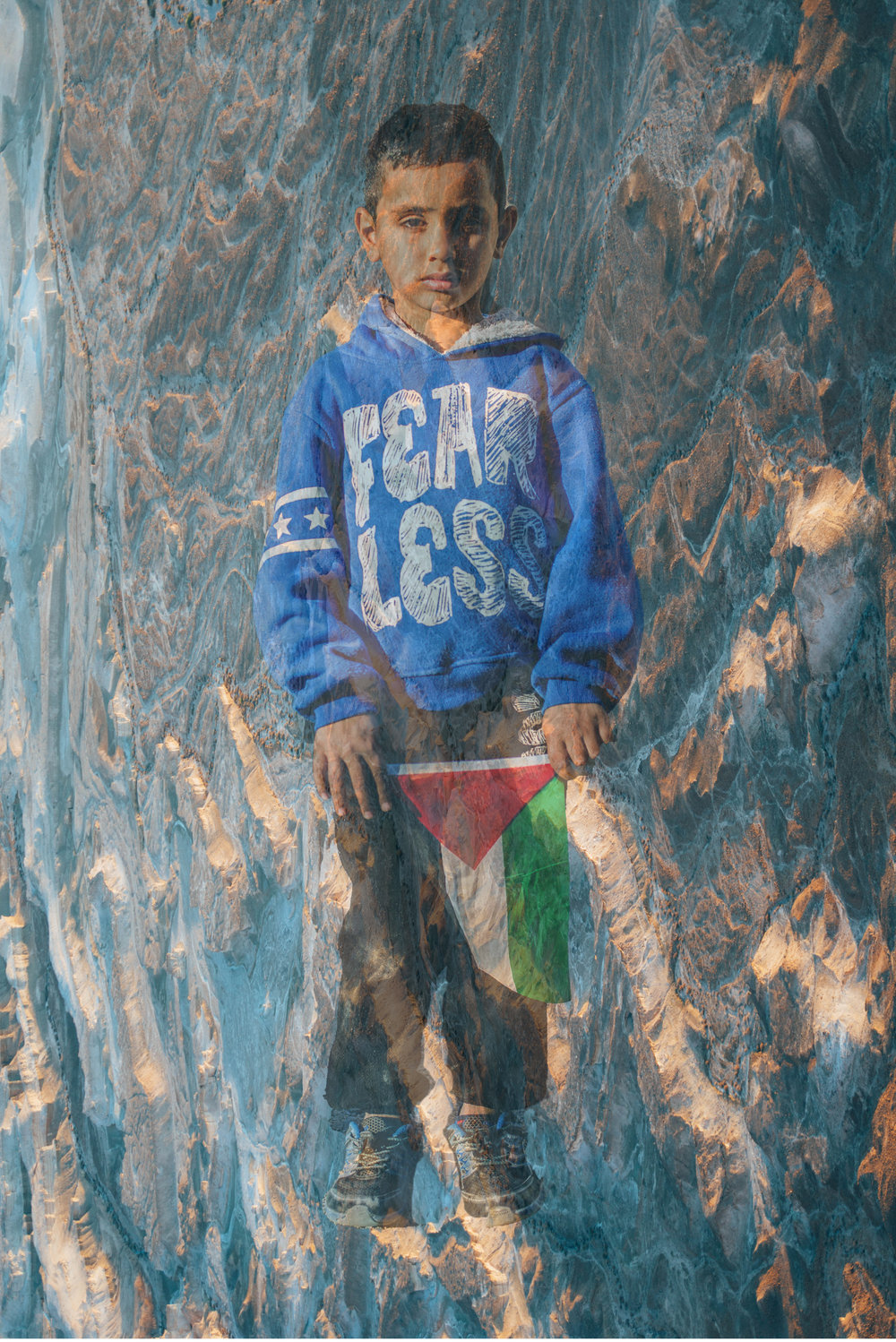 A boy holds a Palestinian flag with Masada superimposed on his portrait.