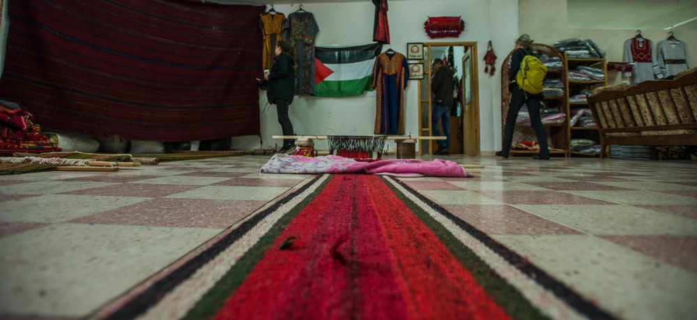 Traditional carpets lay on the floor of the Women in Hebron cooperative in Idna. The women of the cooperative pass down their skills from their previous generations to continue the traditional way of making their handicrafts.