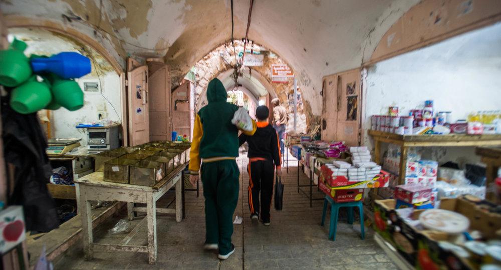 Boys walk through the Old City Hebron Market in H1.