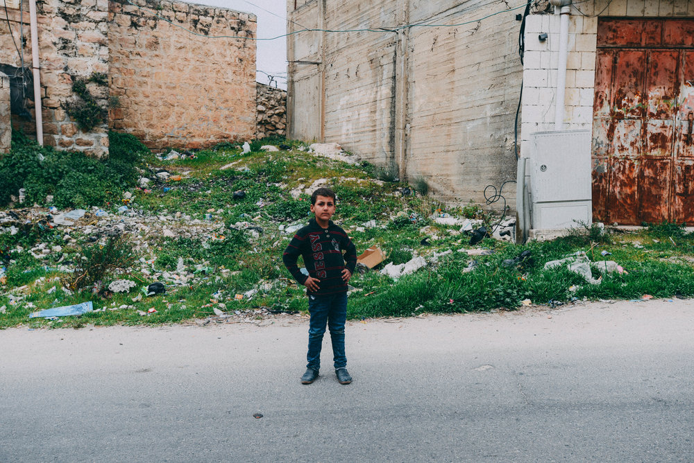 A young Palestinian boy poses for a portrait in the occupied H2 zone where Palestinians live near the Ibrahimi Mosque as refugees.