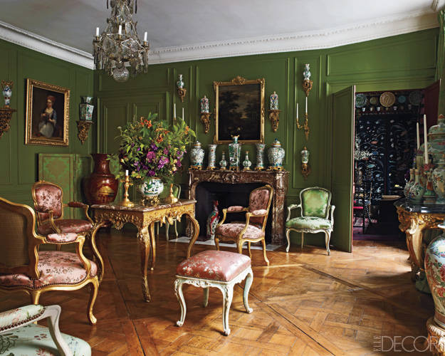 In the drawing room of fashion designer Andrew Gn's Paris apartment, silk-covered Louis XV gilt armchairs surround a Régence table, and a pair of Louis XV armchairs upholstered in a silk brocade flanks a marble mantel from a château in Brittany; the Chinese porcelains are from the Transitional and Khang Hy periods, and the chandelier is 18th-century Swedish.