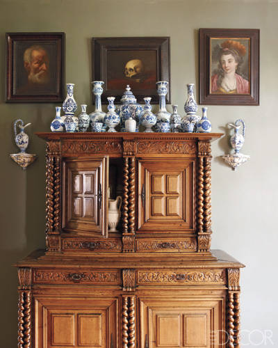 A French provincial walnut cabinet in the entrance hall with a collection of 17th- and 18th-century delft, Nevers, Lille, and Chinese porcelains.