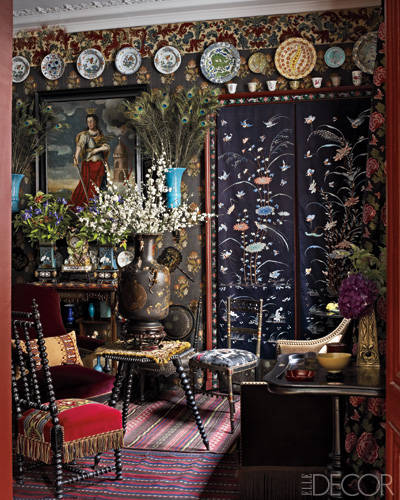 In the bedroom's sitting area, an antique Majorelle vase is filled with 19th-century Chinese Peking glass cherry blossoms, 18th-century Chinese embroidered-silk panels cover a cabinet, and antique Chinese and French Iznik-style plates line the wall; the ebonized chair and table are 19th-century French and English, respectively.    See the full gallery here.