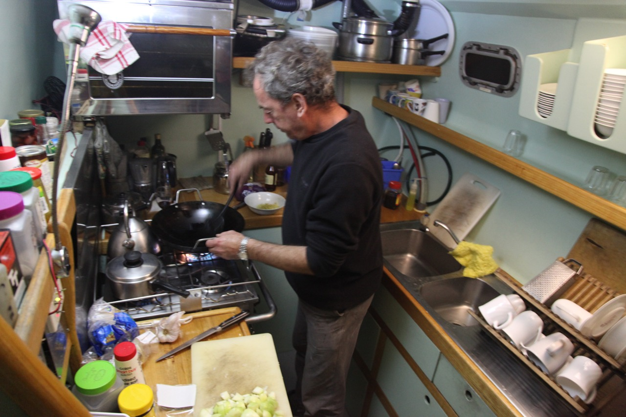 Captain (Garry McKechnie) of Pelican1 cooking in the galley- stir-fry tonight.