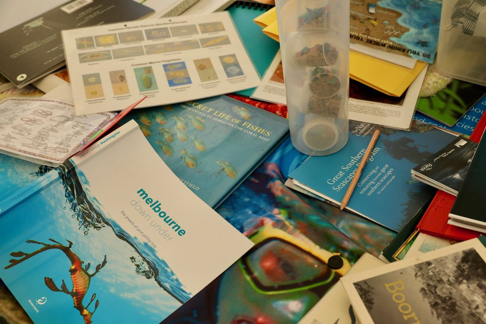 Books. pamphlets and sand with micro plastics make up the composition of the table in Pelican1's sea classroom.