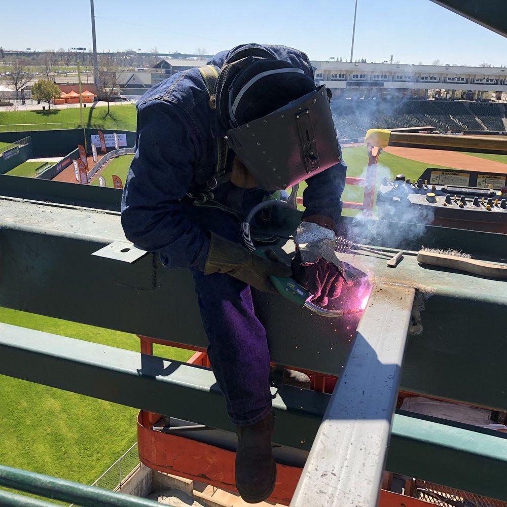 Kasdan welding structural cross-members in the Raley Field Scoreboard Tower.