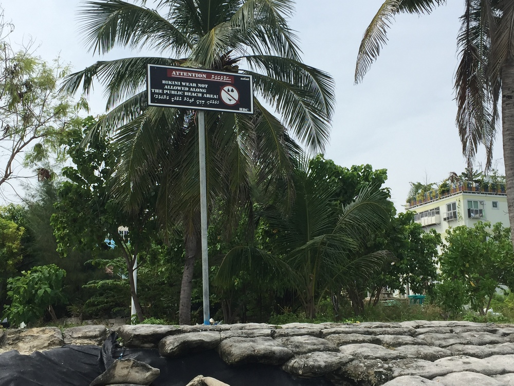 A sign telling tourists to cover up at the beach. Many Maldivians, who are all Muslims, feel uncomfortable at the beech when people wear bikinis, which they consider to be a form of public nudity.