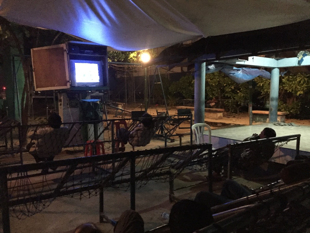 This is a public tv in the main park of the capital. It's a nice place to watch the evening news and the people who gather usually chat about it afterwords. Men play chess here all day and those hammock seat things are super comfortable to read in.